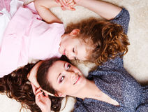 Little girl and mother lying on the carpet Stock Photos