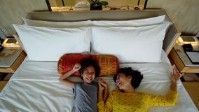 Little girl and mother lying down on bed