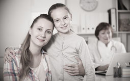 Little girl and mother with mature medical worker. In medical center stock photography