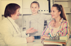 Little girl and mother with mature medical worker. In medical center royalty free stock images