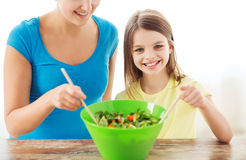 Little girl with mother mixing salad in kitchen Royalty Free Stock Photography