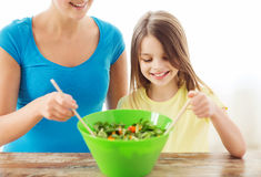 Little girl with mother mixing salad in kitchen Stock Photos