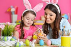 Girl with mother painting eggs. Little girl with mother painting eggs for Easter holiday Stock Photography