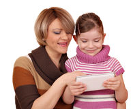 Little girl and mother play with tablet Stock Photos