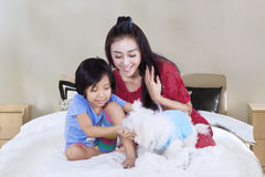 Little girl and mother playing dog on bed Royalty Free Stock Photo