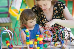 Little girl and mother playing with educational toy Stock Photos