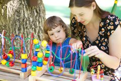 Little girl and mother playing with educational toy. Royalty Free Stock Photos