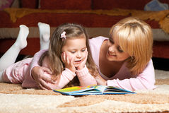 Little girl with mother reading book Stock Photo