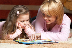Little girl with mother reading book. Sweet little girl with mother reading book royalty free stock images