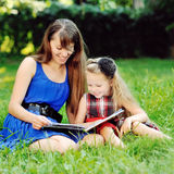 Little girl with mother reading a book in a summer park Stock Images
