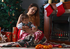 Little girl with mother in the room with Christmas decorations Stock Photos