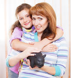 Little girl and mother saving money in a piggybank. Indoor portrait Stock Photography