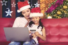 Little girl and mother shopping online with laptop. Picture of little girl and her mother holding a credit card while shopping online at Christmas time Stock Image