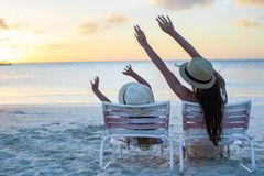 Little girl and mother sitting on beach chairs at Royalty Free Stock Photography