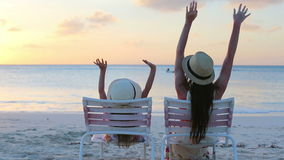 Little girl and mother sitting on beach chairs at sunset stock video footage