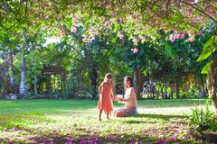 Little girl with mother sitting in the lush garden Royalty Free Stock Photos