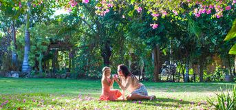 Little girl with mother sitting in the lush garden Royalty Free Stock Images