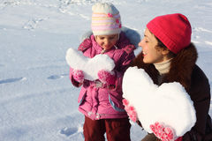 Little girl and mother with snowy hearts Stock Photo