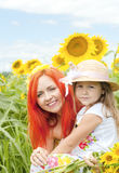 Little girl and mother with sunflowers in a summer  day. Royalty Free Stock Images