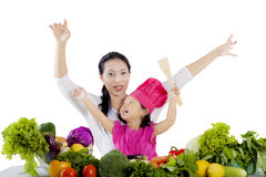 Little girl and mother with vegetables on studio Royalty Free Stock Photo