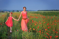 Little girl with mother walking on the poppy field stock photos