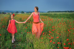 Little girl with mother walking on the poppy field royalty free stock images