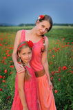 Little girl with mother walking on the poppy field stock image