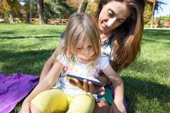 Little girl and mother watching mobile sitting on grass Royalty Free Stock Images