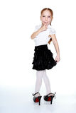 Little girl in mothers shoes on the white background Royalty Free Stock Photography