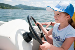 Little girl on motorboat. Happy little girl driving motorboat stock images