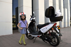 Little girl with motorcycle. On shopping Stock Image