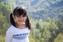 Little girl on mountains vacation. Portrait of girl with mountain in background stock images