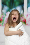 Little girl muffled in blanket yawns Stock Photo