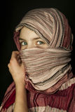 Little girl muffled in a shawl. On the black background Stock Photography