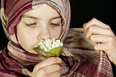 Little girl muffled in a shawl. With flowers Stock Images