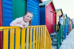 Little girl at Muizenberg beach. Adorable little girl playing at famous colorful huts of Muizenberg beach near Cape Town in South Africa Royalty Free Stock Image