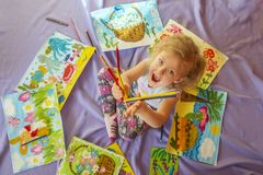 A little girl with multi-colored pencils in her hands on the floor among many of her drawings. stock images
