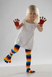 Little girl in multi-coloured clothes. Little girl in white dress, multi-coloured stockings and colour gloves royalty free stock photo