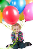 Little girl with multicolored air balloons sitting Royalty Free Stock Photos
