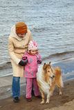 Little girl with mum and dog walk on autumn beach Royalty Free Stock Images