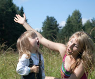 Little girl with mum sing a song. On meadow Stock Photo