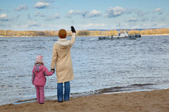 Little girl and mum are situated on bank of river Stock Photos