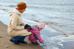 Little girl with mum walk on autumn beach Stock Images