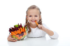 Little girl munching on a carrot stick. Holding bowl of vegetables stock photography