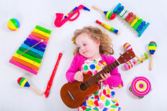 Little girl with music instruments Stock Photo