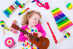 Little girl with music instruments Stock Image