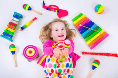 Little girl with music instruments Stock Photos