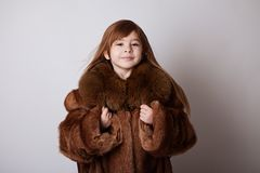 Little girl in my mother`s brown long coat. Little girl in mother`s brown long coat, playing, fooling around. White background Royalty Free Stock Image
