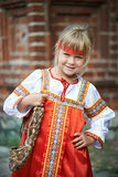 Little girl in national costumes in Russian village. On summer day stock photo