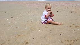 Girl in Ukrainian Costume Embroidery on Beach. Little girl in the national Ukrainian costume embroidery child takes a stone stands up and walks on the beach stock footage